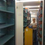 Student worker aka Kelsi moving rows of books